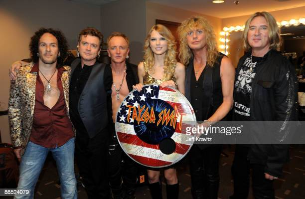 Musicians Rick Savage, Vivian Campbell, Joe Elliott, Phil Collen, and Rick Allen of Def Leppard poses with singer Taylor Swift during the 2009 CMT...