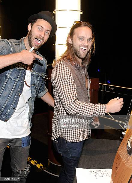 Musicians Rickard Goransson and Chad Wolf of Carolina Liar autograph a guitar backstage at the GRAMMYs Dial Global Radio Remotes during The 54th...