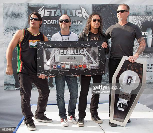Musicians Robert Trujillo Lars Ulrich Kirk Hammett and James Hetfield of Metallica are handling a platinum disc for more than 80000 copies sold in...