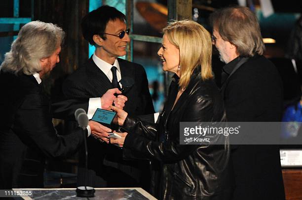 Musicians Robin Gibb and Barry Gibb of The Bee Gees speak with inductees AnniFrid Prinsessan Reuss and Benny Andersson of ABBA onstage at the 25th...