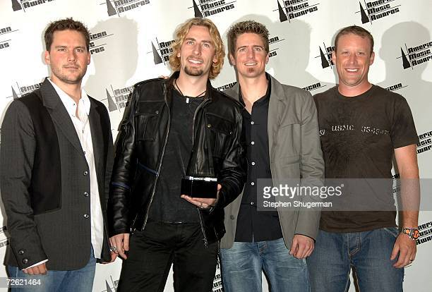Musicians Ryan Peake Chad Kroeger Daniel Adair and Mike Kroeger of the band Nickelback pose in the press room at the 2006 American Music Awards held...
