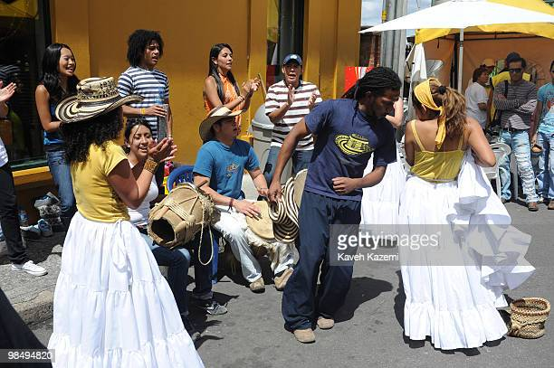Musicians sing and dance while playing instruments on a busy street market in the city Bogota formerly called Santa Fe de Bogota is the capital city...