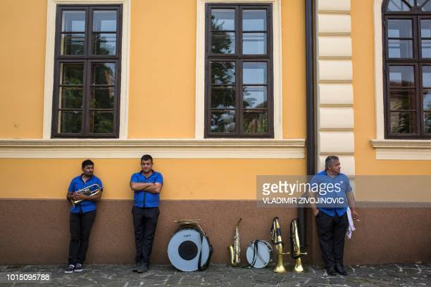 Musicians stand with their instruments during the trumpet and brass band festival in the Serbian village of Guca about 160 km south of Belgrade on...