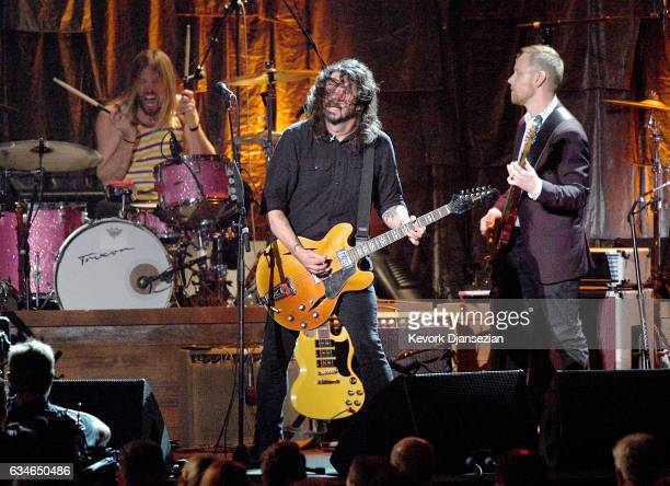 Musicians Taylor Hawkins Dave Grohl and Nate Mendel of Foo Fighters perform onstage during MusiCares Person of the Year honoring Tom Petty at the Los...