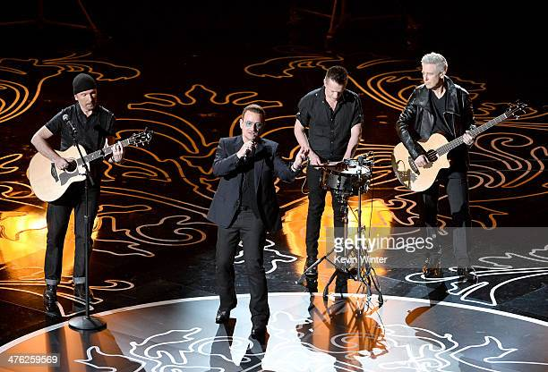 Musicians The Edge Bono Larry Mullen Jr and Adam Clayton of U2 perform onstage during the Oscars at the Dolby Theatre on March 2 2014 in Hollywood...