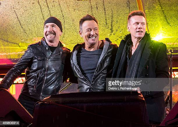 Musicians The Edge of U2 Bruce Springsteen and Larry Mullen Jr of U2 perform for World AIDS Day Concert at Times Square on December 1 2014 in New...