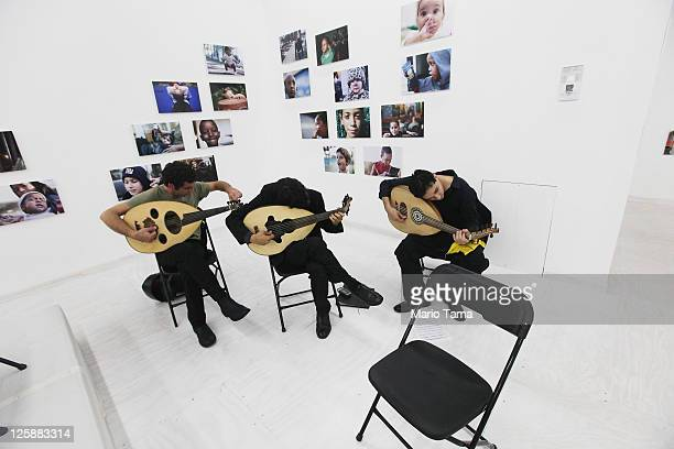 Musicians tune their instruments in front of the opening exhibition of photographer Danny Goldfield's 'NYChildren' project at the grand opening of...