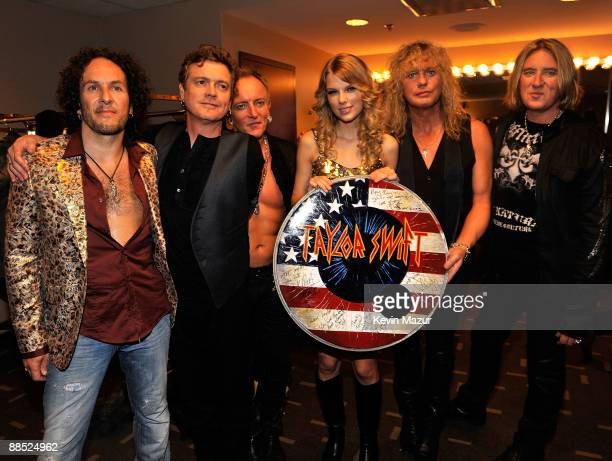 Musicians Vivian Campbell, Rick Allen, Phil Collen, Rick Savage, and Joe Elliott of Def Leppard poses with singer Taylor Swift at the 2009 CMT Music...