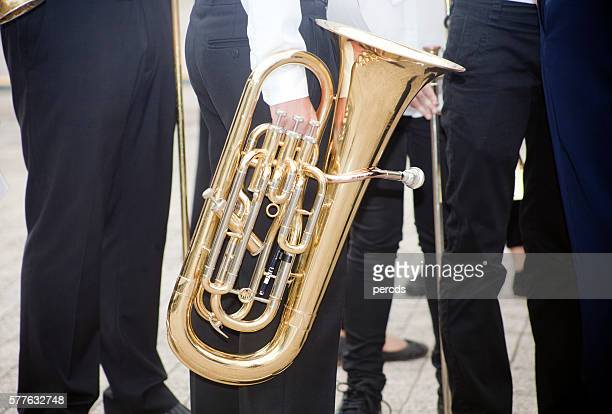 Musicians walking with a tuba.