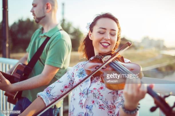 músicos con violín y guitarra - violin fotografías e imágenes de stock