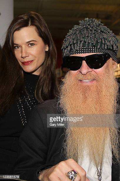Musician/vocalist Billy Gibbons of ZZ Top signs bottles of Pura Vida Tequila as his wife Gilligan Gibbons looks on at Gabriel's Liquor on January 28...