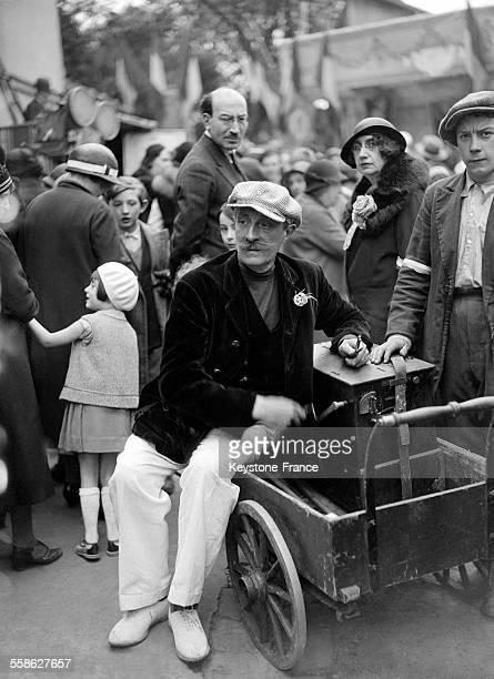 Musicien ambulant avec orgue de Barbarie lors de la fête à Montmartre au Moulin de la Galette au profit des 'Poulbots' à Paris France circa 1930