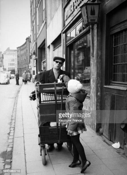 Musicien jouant de l'orgue de Barbarie dans les rues de Cologne Allemagne le 8 avril 1965