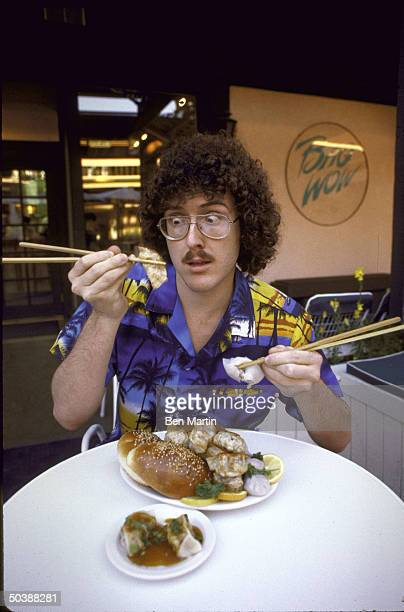 Music/Video Parodist Al Yankovic holding food with chopsticks at Bao Wow' Chinese restaurant in which he has invested