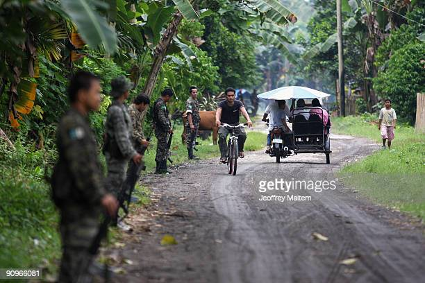 Musilm rebels secure a road inside their camp after Ibrahim Murad, chief of the Moro Islamic Liberation Front, warns anarchy if peace talks between...