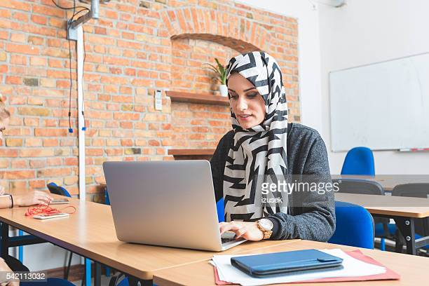 Musilm young woman working on laptop