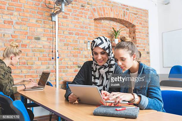 Musilm young woman working on laptop with friend