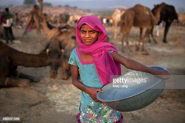 Muskan a young beautiful greeneyed girl from a village near Ajmer is collecting camel dung as combustible at the Pushkar fair in Rajasthan India