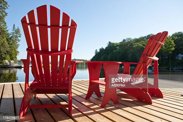 muskoka chairs on a sunny morning - waterfront stock pictures, royalty-free photos & images