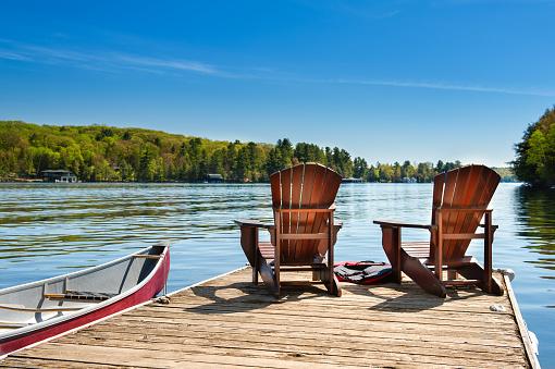 Muskoka chairs on a wooden dock 1158195529