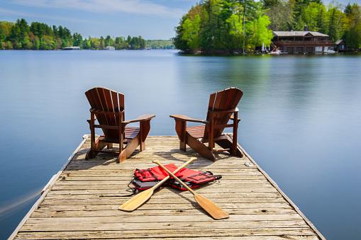 Muskoka chairs on a wooden dock 962759494