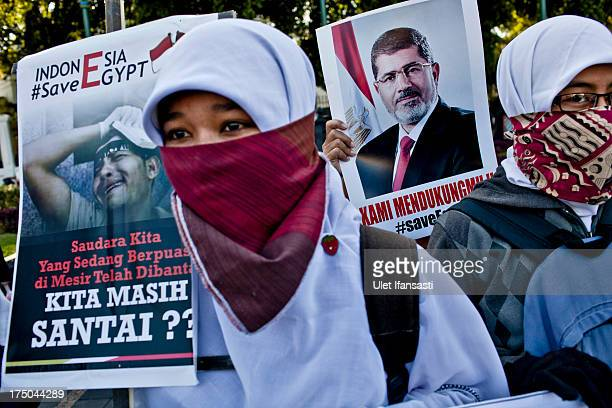Muslim activists from the Youth Alliance Care for the Muslim World hold posters of deposed Egyptian President Mohammed Morsi during a protest against...