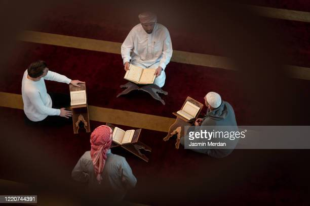 muslim adults learning koran together in mosque - koran stock pictures, royalty-free photos & images
