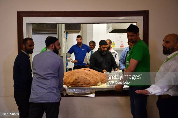 Muslim Aid staff and volunteers work as they attempt to construct and cook the world's largest samosa at the East London Mosque in London on August...