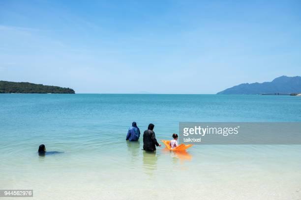muslim at cenang beach, langkawi, malaysia - muslim woman beach stock photos and pictures