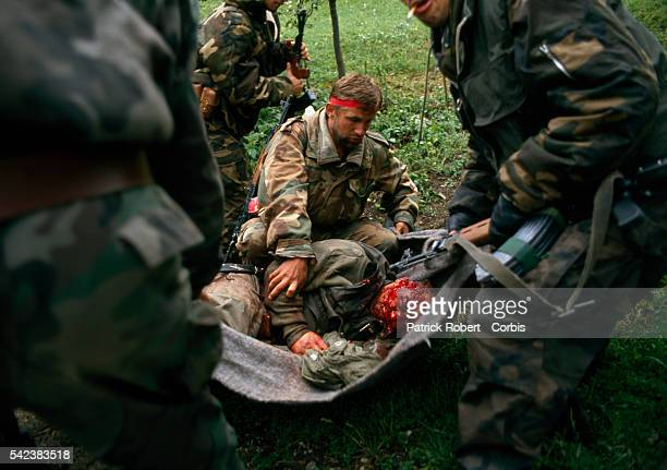 Muslim Bosnian soldiers assist an injured friend on the eastern frontline of Bandol in the Yugoslavian Civil War Conflict among the Croats Serbs and...