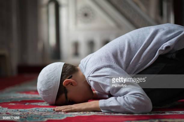 muslimische jungen beten in der moschee - islam stock-fotos und bilder