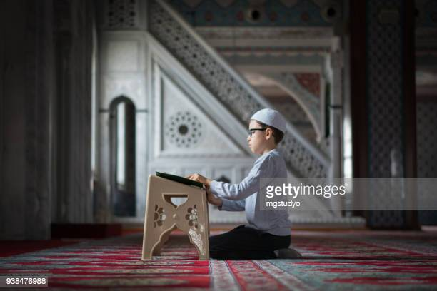 muslim boy reading the holy koran in mosque - koran stock pictures, royalty-free photos & images