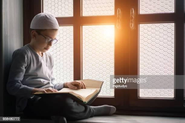 Muslim boy reading The Holy Koran in Mosque
