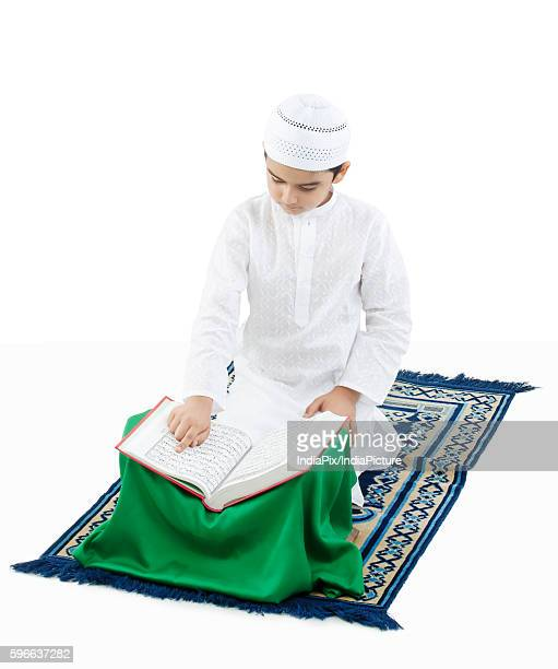 muslim boy reading the quran - holy quran stock pictures, royalty-free photos & images