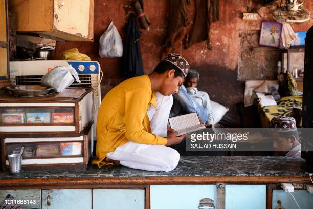 A Muslim boy reads a copy of the Koran in a closed shop during the holy fasting month of Ramadan under a governmentimposed nationwide lockdown to...