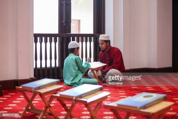 een islamitische jongen reciteren van heilige quran aan zijn vader in een moskee - moskee stockfoto's en -beelden