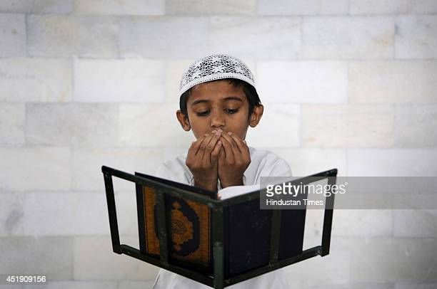 Muslim boy reciting verses from Holy Book during a Quran class on the 10th day of Ramadan at a Mosque on July 9 2014 in Noida India Muslims...