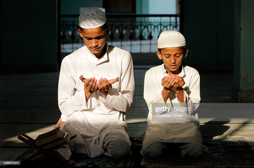 Muslim boys making dua after reciting verses from Holy Book
