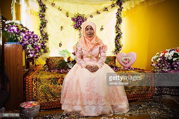 Muslim bride on her bed adorned with flowers for her wedding night