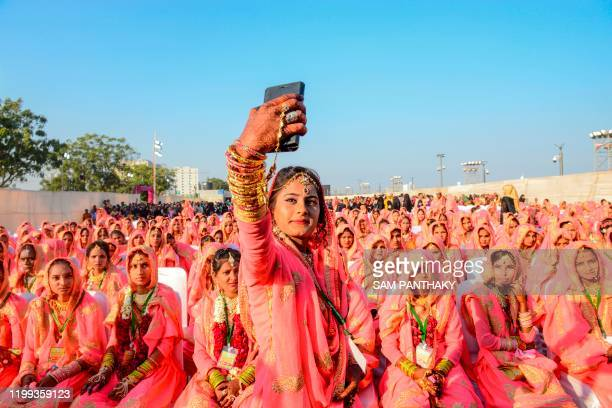 Muslim bride takes a selfie with her mobile phone as she participates in an 'All Religion Mass Wedding' ceremony at Sabarmati Riverfront in Ahmedabad...