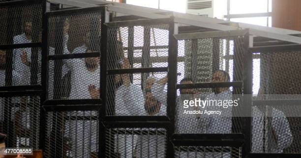 Muslim Brotherhood leader Mohamed Badie and 47 other defendants stand behind bars during the trial of Brotherhood members at a courtroom on March 6,...