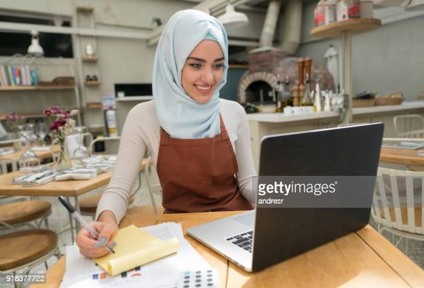 Muslim business owner doing the books at a restaurant