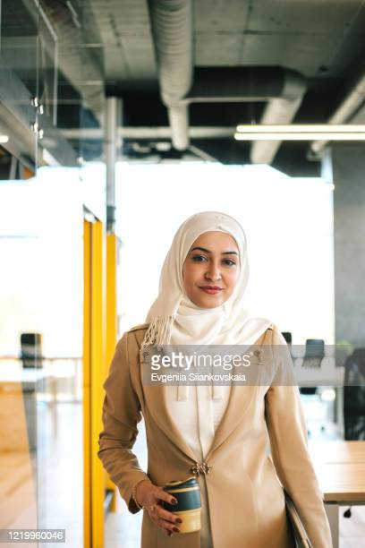 muslim business woman coming to office with laptop and reusable coffe cup. - middle east stock pictures, royalty-free photos & images