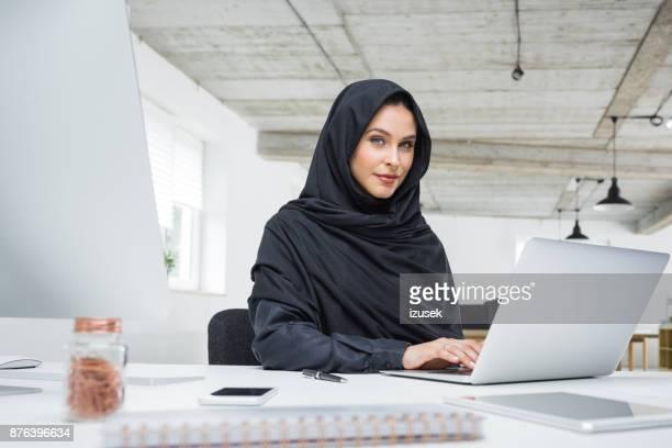 Muslimische Geschäftsfrau arbeiten am Laptop im Büro