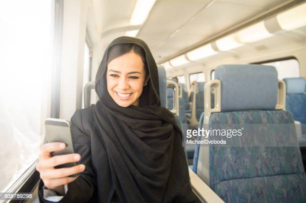 muslim business women commuting on the train - nikab stock pictures, royalty-free photos & images