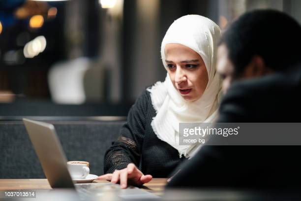 muslim businesswoman and african american businessman working together in cafe - turkey middle east stock pictures, royalty-free photos & images