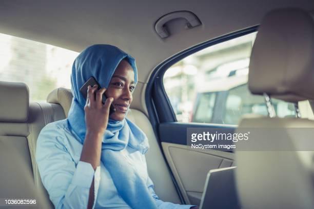 Eine muslimische geschäftsfrau in ein Taxi, mit Laptop und Handy