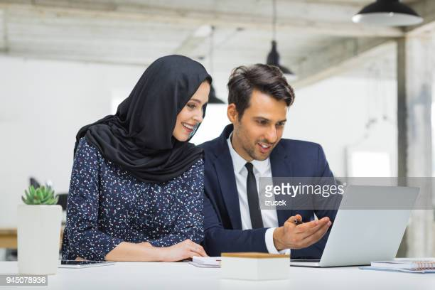 muslim businesswoman in discussion with colleague - izusek stock pictures, royalty-free photos & images