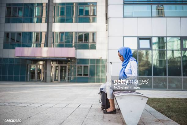 a muslim businesswoman on a business trip, sitting on the bench using a laptop - palestinian stock pictures, royalty-free photos & images