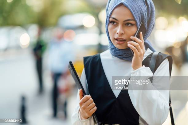 muslim businesswoman talking on phone ain street - middle east stock pictures, royalty-free photos & images